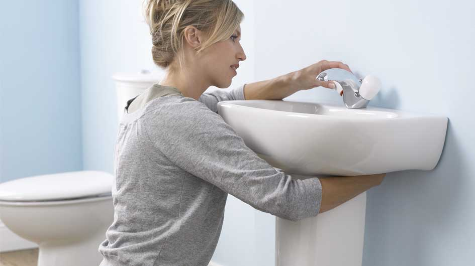 Lady fixing sink fauset